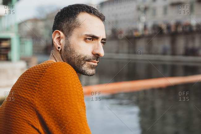 Young man sitting by waterway in an urban city