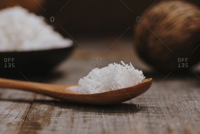 Coconuts with coconuts flakes on wooden table.