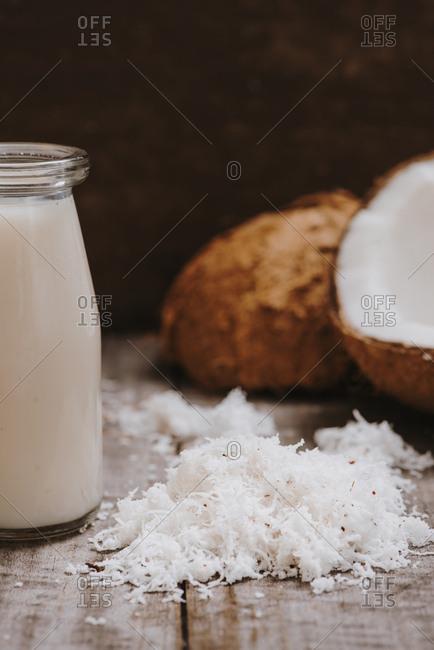 Coconut milk in bottle with broken coco on wooden