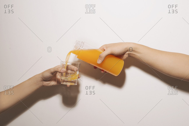 Hand pouring orange juice from jug with ice into glass isolated on white background