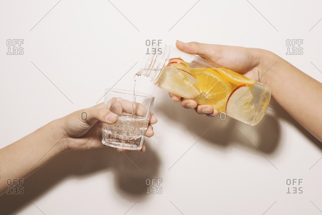 Male hand pours detox water into glass. Detox water, fitness, healthy nutrition diet concept. Fresh lemon cucumber mint detox drink in glass on white wooden table