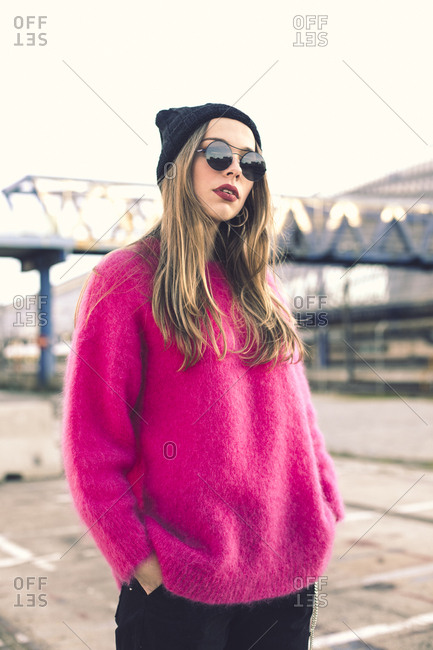 Portrait of fashionable young woman wearing sunglasses- cap and pink knit pullover