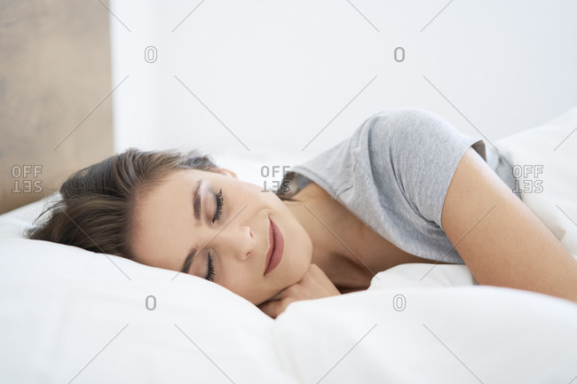 Young woman resting on bed- with eyes closed