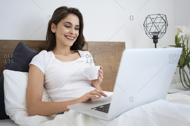 Woman having coffee in bed using laptop- laughing