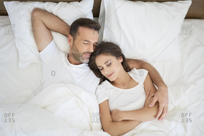 Couple lying in bed- sleeping with arms around