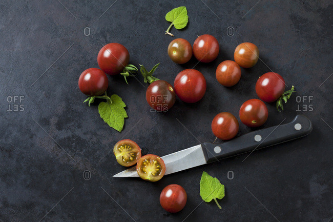 Whole and sliced ripe tomatoes 'Black Cherry'- leaves and kitchen knife on dark ground