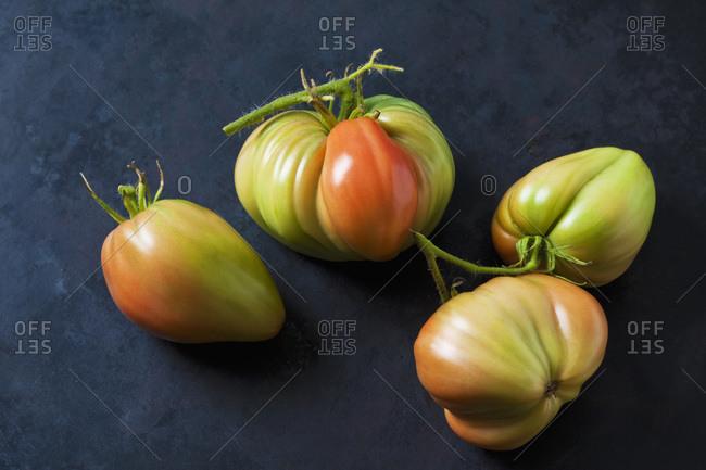 Four Oxheart tomatoes on dark ground