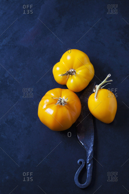 Three tomatoes 'Golden Jubilee' and a knife on dark background