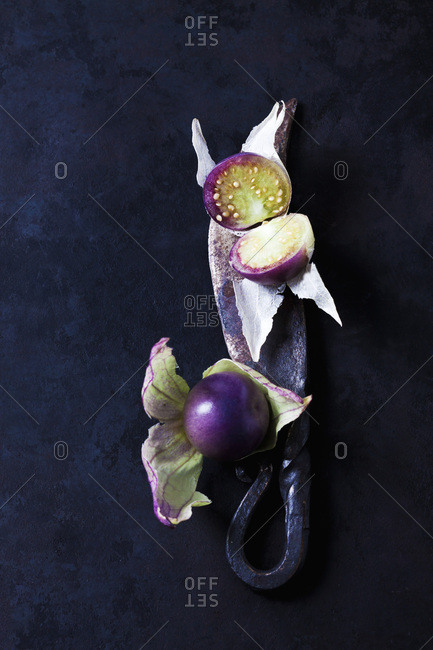 Sliced and whole tomatillos and a knife on dark background