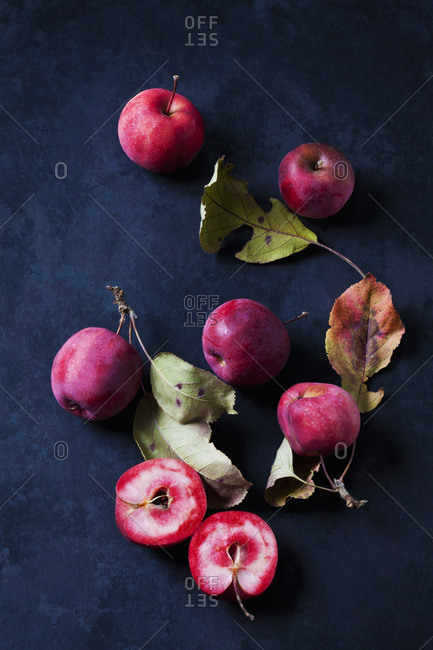 Sliced and whole red-fleshed apples on dark ground