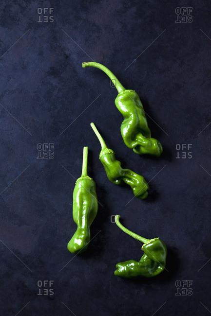Green pepperonis on dark background