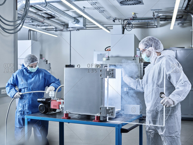 Chemists working in industrial laboratory clean room