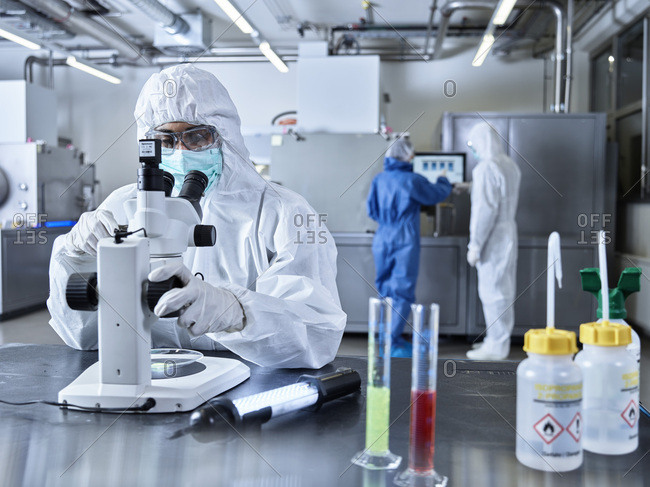 Chemists working in industrial laboratory- wearing protective clothing- using microscope