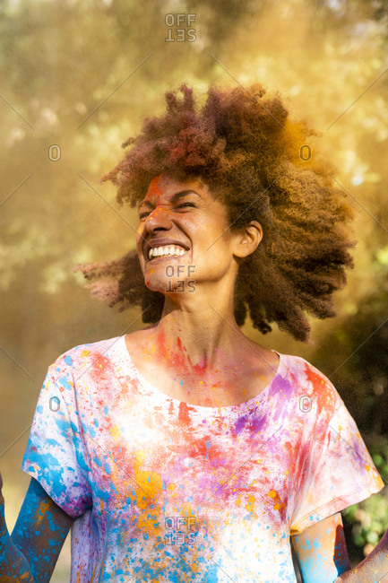 Woman shaking her head- full of colorful powder paint- celebrating Holi- Festival of Colors