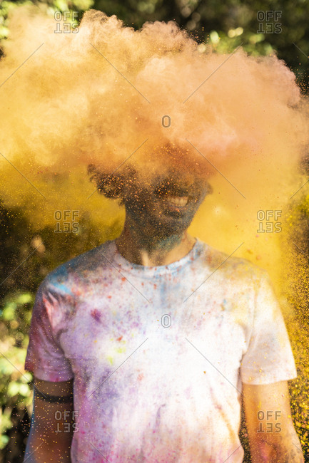 Man shaking his head- full of colorful powder paint- celebrating Holi- Festival of Colors