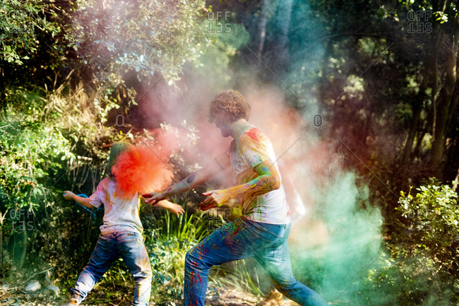 happy family celebrating Holi festival in the forest- throwing colorful powder paint