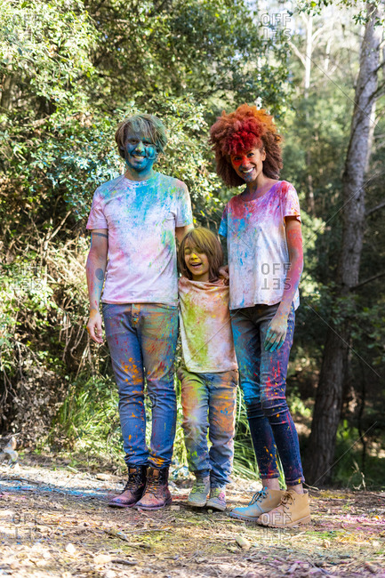 Family in the forest- full of colorful powder paint- after celebrating Holi- Festival of colors