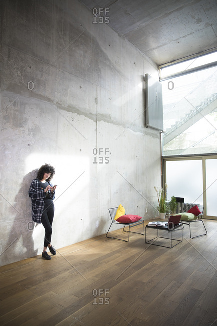 Woman leaning against concrete wall in a loft using cell phone