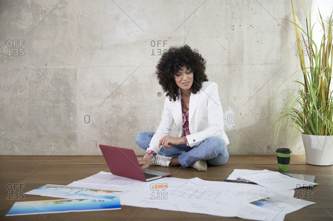 Businesswoman sitting on the floor in a loft working with laptop and documents