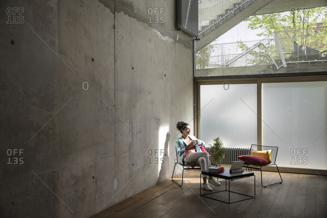 Businesswoman sitting in a loft at concrete wall having a break