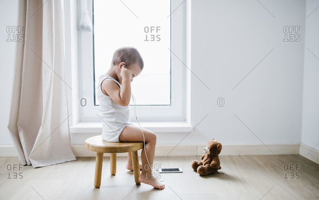 Toddler boy sitting on stool at home using smartphone and earphones