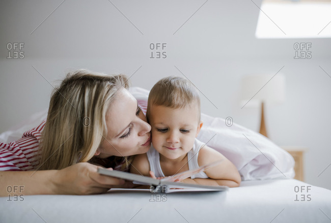 Mother kissing toddler son lying in bed at home reading a book