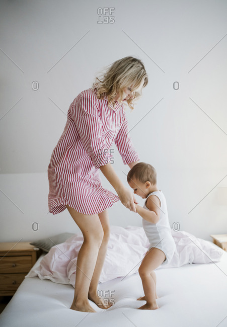 Mother playing with toddler son on bed at home