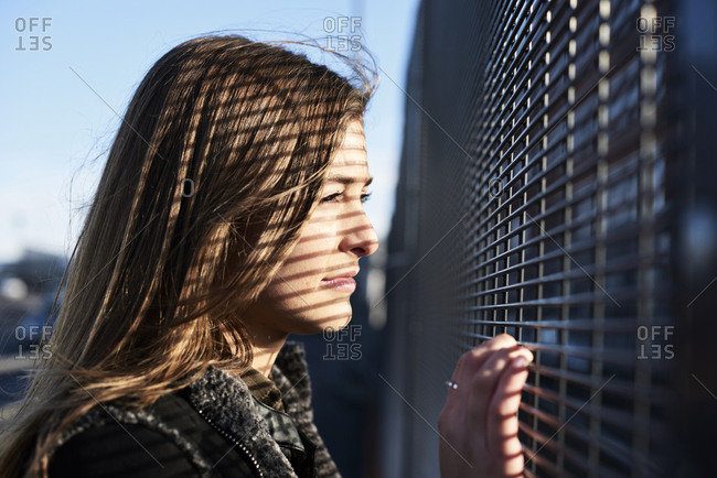 Portrait of young woman with shades on her face looking through metal fence