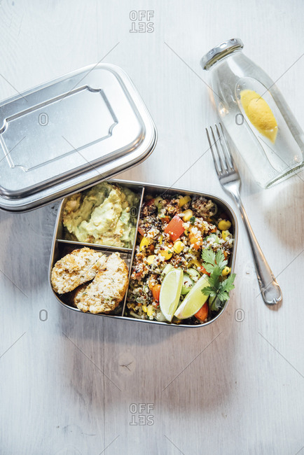 Bento box of quinoa salad with vegetables and lime- avocado cream and cauliflower dumplings