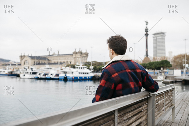Young man wearing casual clothes sitting on a bench at harbor