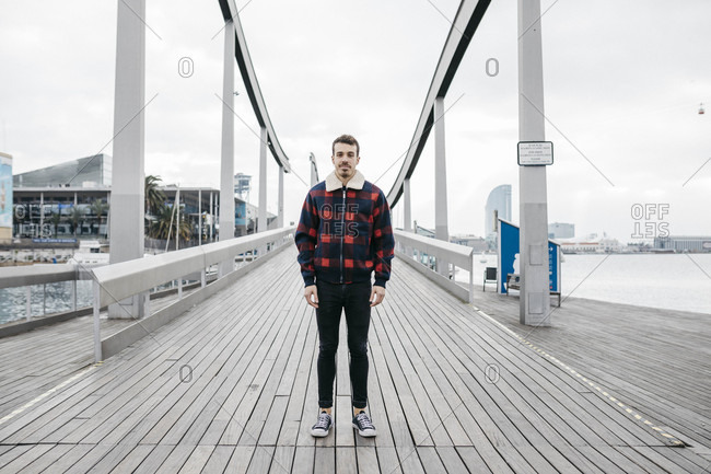 Young man wearing casual clothes standing on a harbor bridge