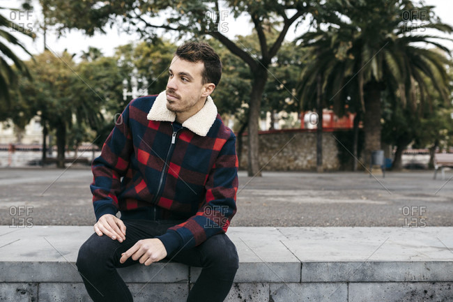 Young man wearing casual clothes sitting on a bench in the city