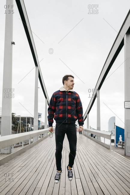 Young man wearing casual clothes jumping on a harbor bridge