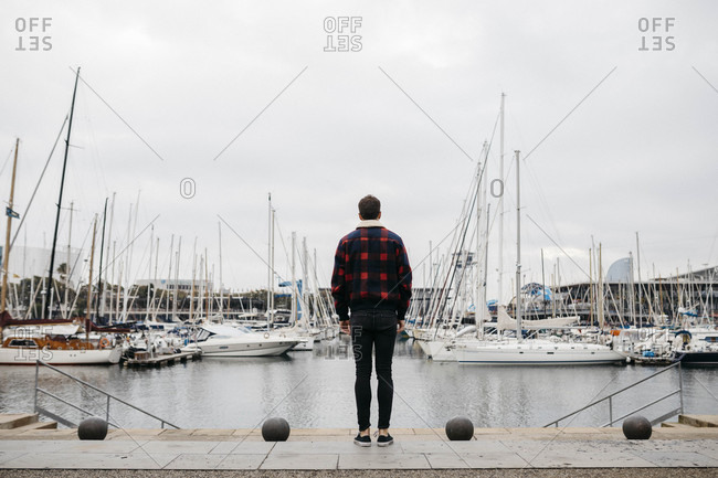 Back view of a young man with casual clothes looking at the harbor