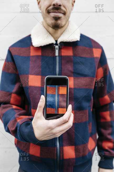 Young man showing a photo on the phone in the colors of his jacket