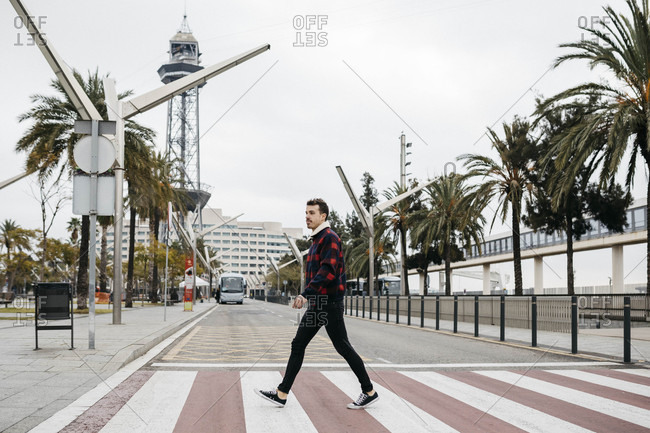 Young man with casual clothes walking on pedestrian crossing in Barcelona