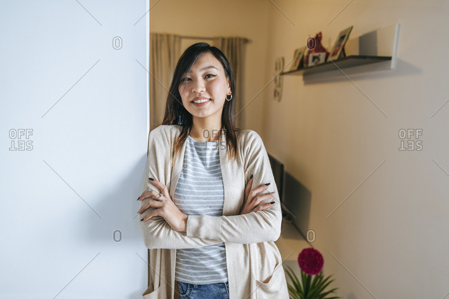 Confident woman leaning against wall with arms crossed- portrait