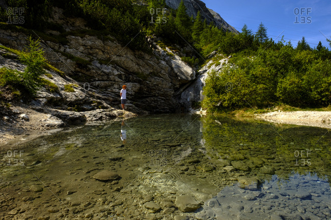 Italy- South Tyrol- Dolomites- young hiker standing on a source
