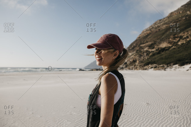 South Africa- Western Cape- Noordhoek Beach- smiling young woman wearing base cap standing on the beach