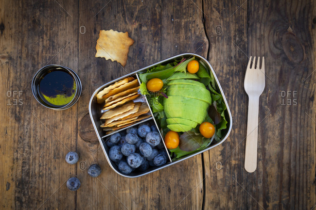 Lunch box of leaf salad- avocado- blueberries- tomatoes and crackers