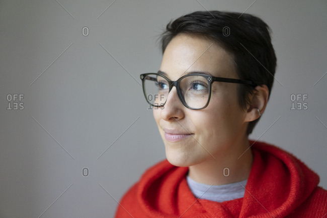 Portrait of a smiling young woman with short hair- wearing glasses