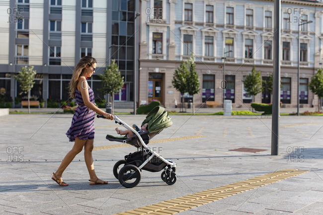 Mother pushing baby in a stroller in the city