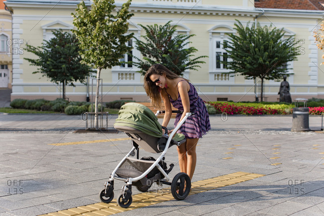 Mother with baby in a stroller in the city