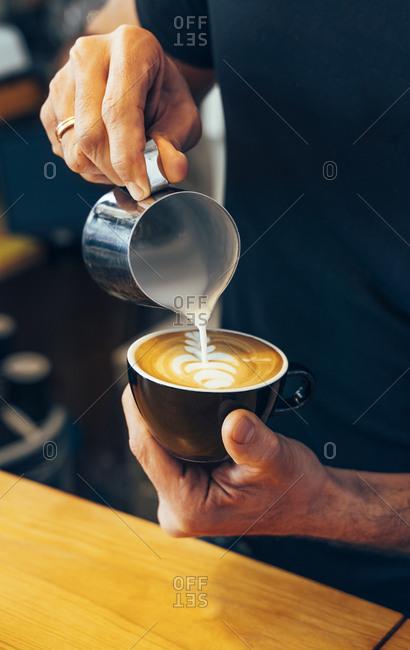 Close-up of barista preparing cappuccino in a coffee shop