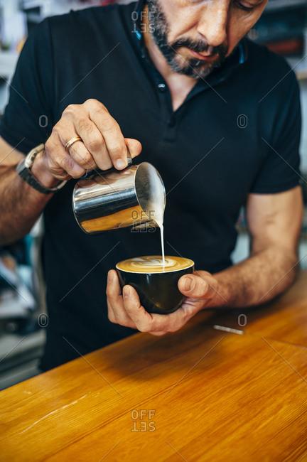 Barista preparing cappuccino in a coffee shop