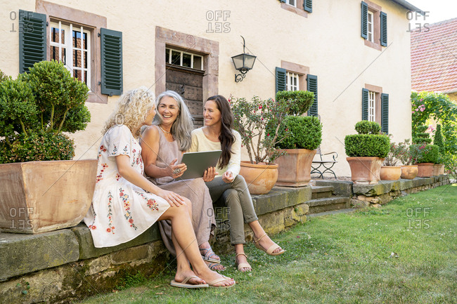 Three happy women of different age sitting in garden using tablet