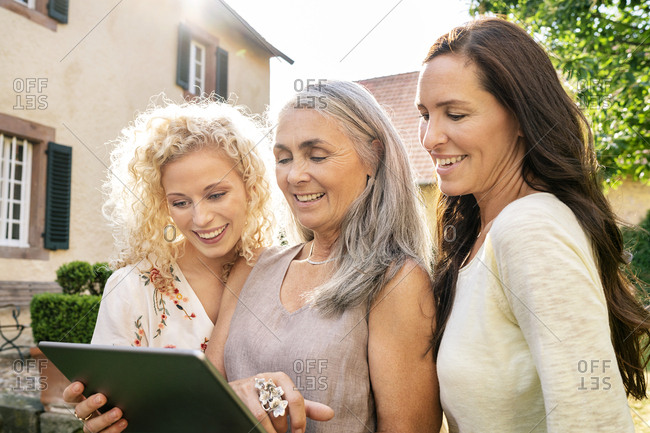 Three smiling women of different age using tablet in garden