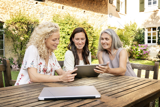 Three women of different age sitting at garden table using tablet