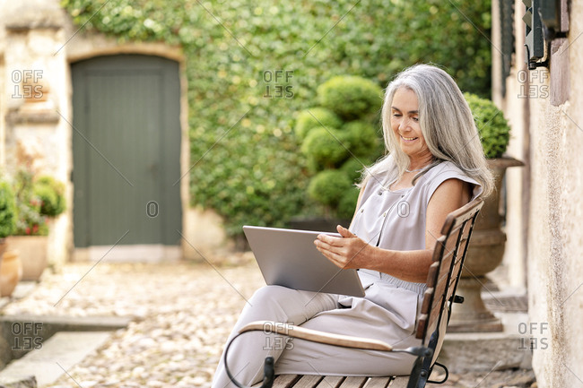 Woman with long grey hair sitting on bench at country house using tablet