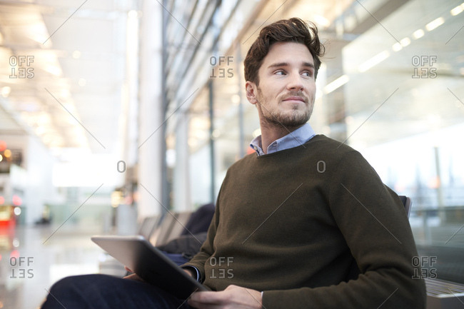 Smiling young businessman with tablet looking around